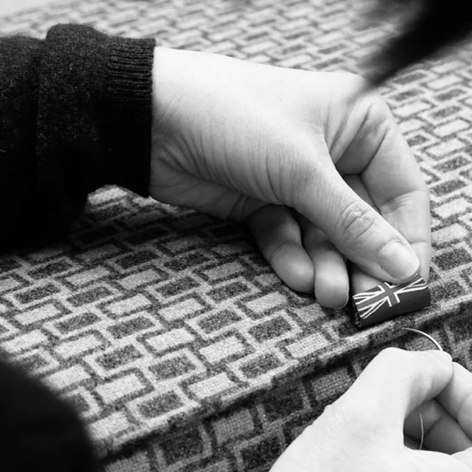 black and white photo of hands stitching a label on furniture